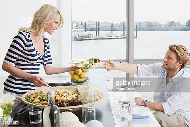Woman passing plate to man