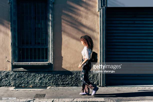 woman passing roller shutters of closed shop, milan, italy - roller shutter stock pictures, royalty-free photos & images