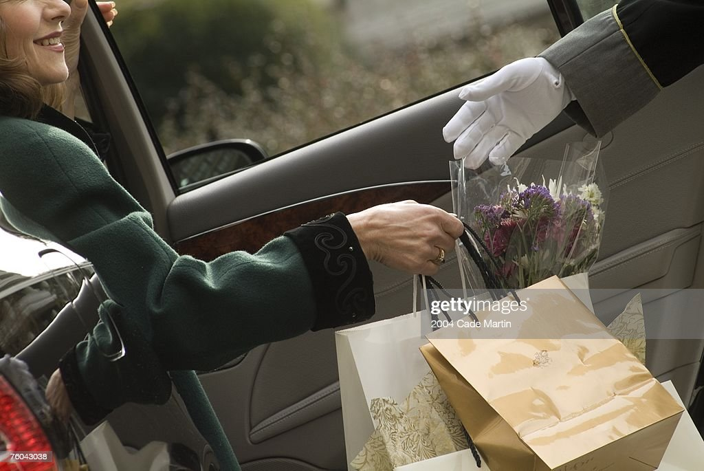 Woman passing shopping bags to valet : Foto de stock