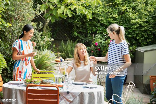 Woman passing wine to friends getting ready for outdoor dinner party.