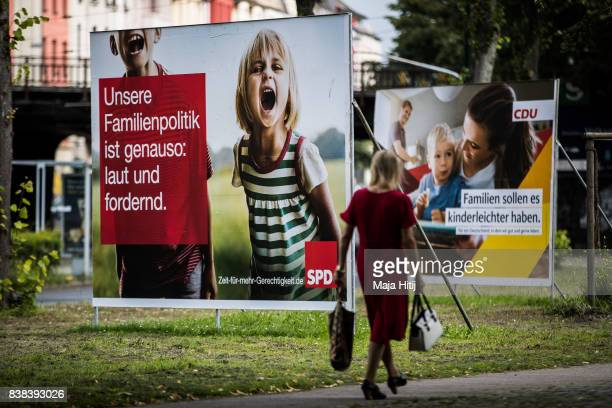 A woman past election campaign billboards of the German Social Democrats and the German Christian Democrats on August 24 2017 in Dusseldorf Germany...