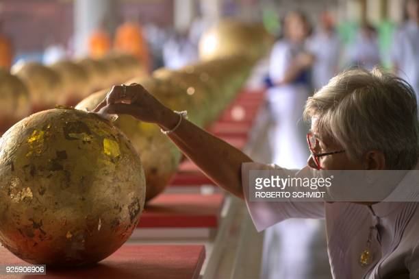 A woman pastes a golden patch to a sphere ahead of evening prayers during Makha Bucha Day celebrations at Wat Phra Dhammakaya temple near Bangkok on...