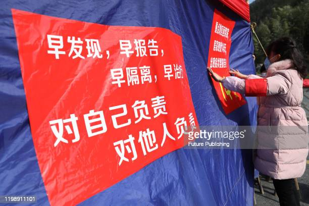 A woman pastes slogans against the coronavirus spread in a village in Hangzhou in east China's Zhejiang province Wednesday Feb 05 2020 PHOTOGRAPH BY...