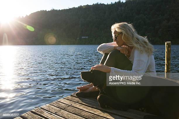 Woman pats dog on lake pier, sunrise