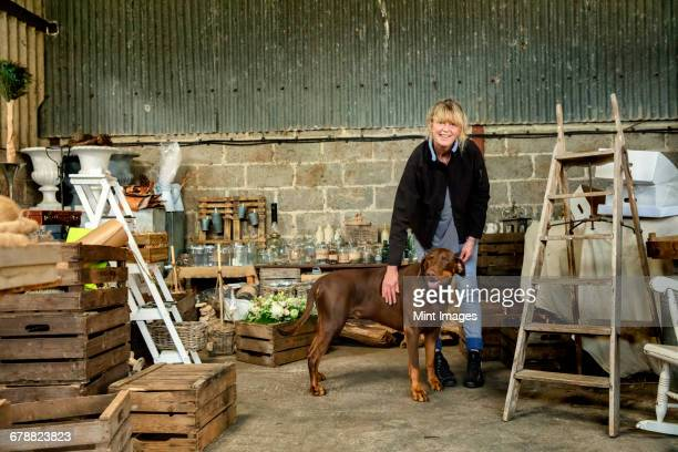 A woman patting a large brown pet dog