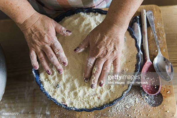 Woman patting crumble mixture into a pie dish, making a fruit crumble pudding.