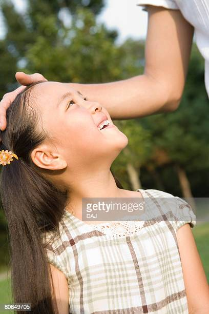 Woman patting girl on head, smiling, summer
