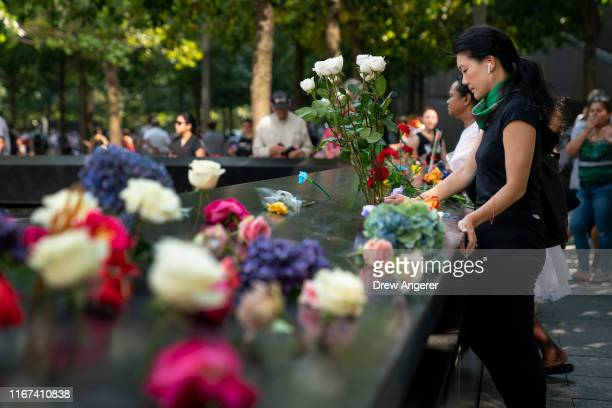 A woman pauses after laying flowers at the National September 11 Memorial on the 18th anniversary of the 9/11 attacks September 11 2019 in New York...