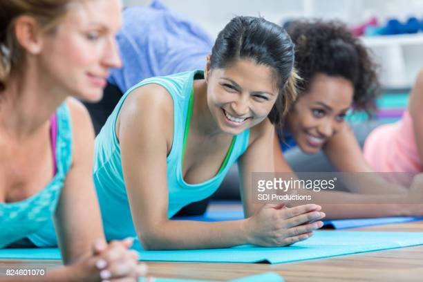 Woman pauses and laughs during floor exercises at gym