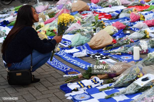 TOPSHOT A woman pauses as she adds flowers to a growing pile of tributes outside Leicester City Football Club's King Power Stadium in Leicester...