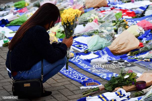 A woman pauses as she adds flowers to a growing pile of tributes outside Leicester City Football Club's King Power Stadium in Leicester eastern...