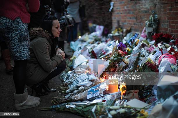 A woman pauses as she looks at the flowers and tributes outside the Oxfordshire home of British pop singer George Michael on December 27 2016 in...