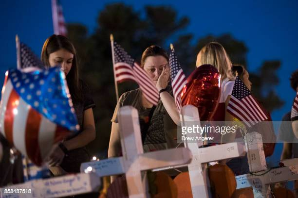 A woman pauses at a makeshift memorial on the south end of the Las Vegas Strip October 6 2017 in Las Vegas Nevada On October 1 Stephen Paddock opened...