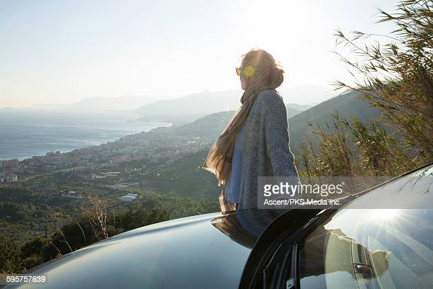 Woman pauses beside car hood,looks out to sea view