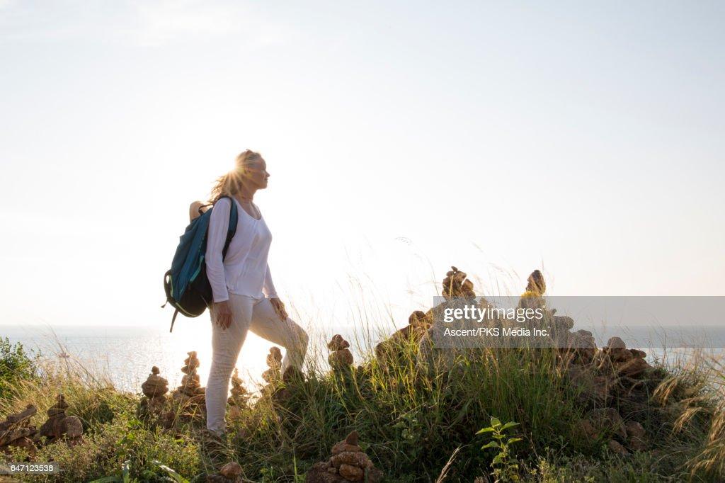 Woman pauses beside Zen rock piles, looks over sea : ストックフォト