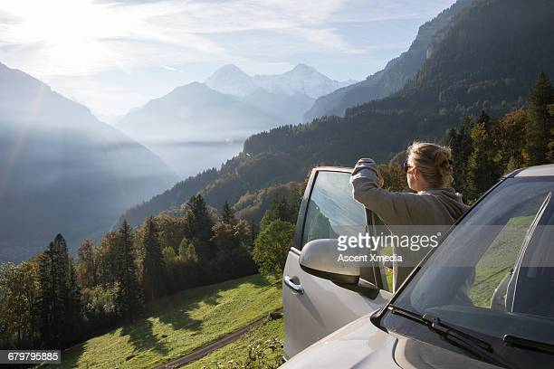 woman pauses by car door, looks out over mtns - autoreise stock-fotos und bilder