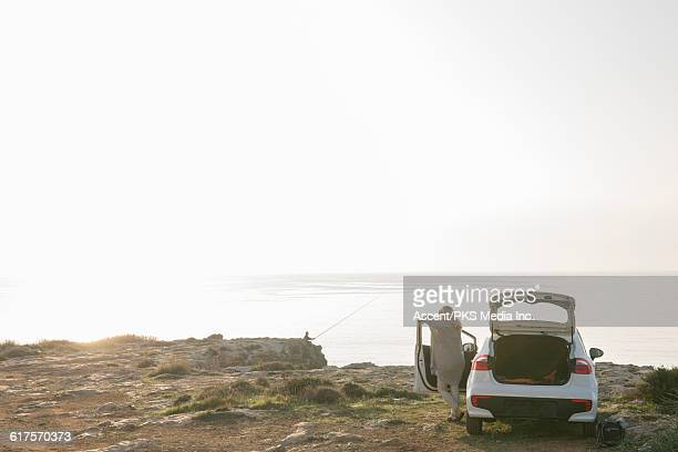 Woman pauses by car door, looks out to sea