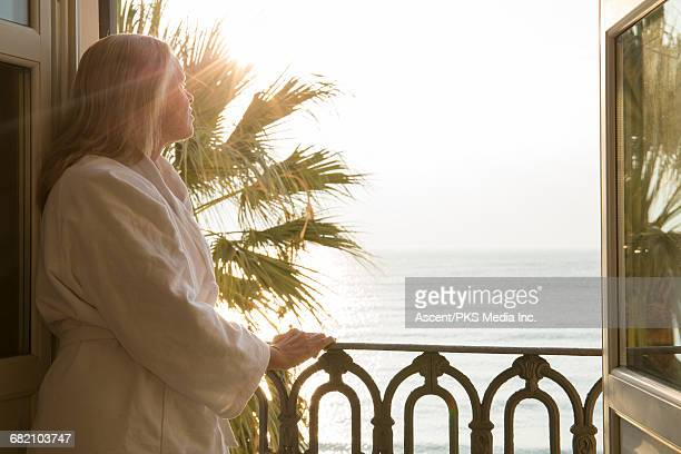 Woman pauses by open window over sea, in bath robe