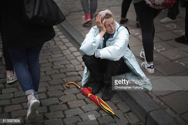 A woman pauses for thought after people observed a one minute silence at the Place De La Bourse in honour of the victims of yesterdays' terror...