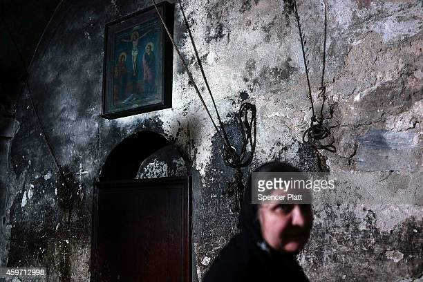 A woman pauses in the Church of the Holy Sepulchre on November 29 2014 in Jerusalem Israel The church is said to be where Jesus was crucified and...