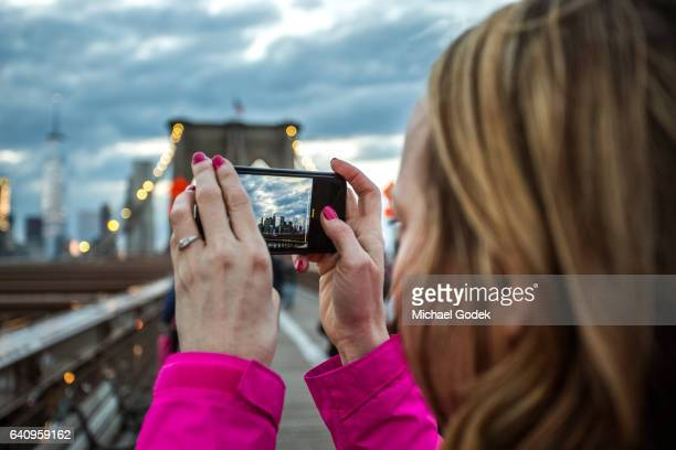 Woman pauses on Brooklyn Bridge to take a photo of the Manhattan skyline at dusk on her phone