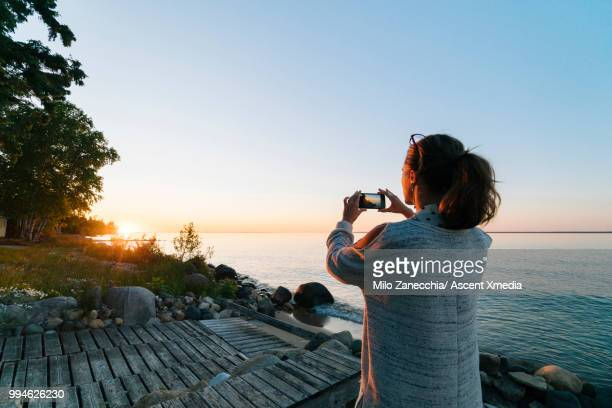 Woman pauses on lakeshore at sunrise, takes pic