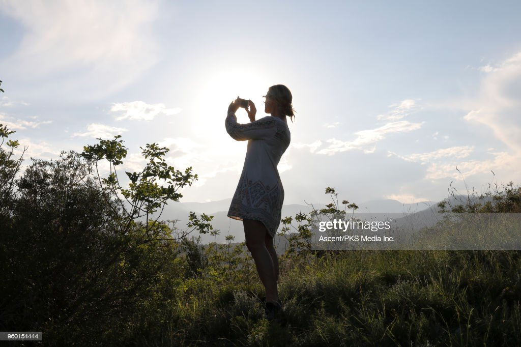 Woman pauses on ridge crest above distant hills : Stock-Foto