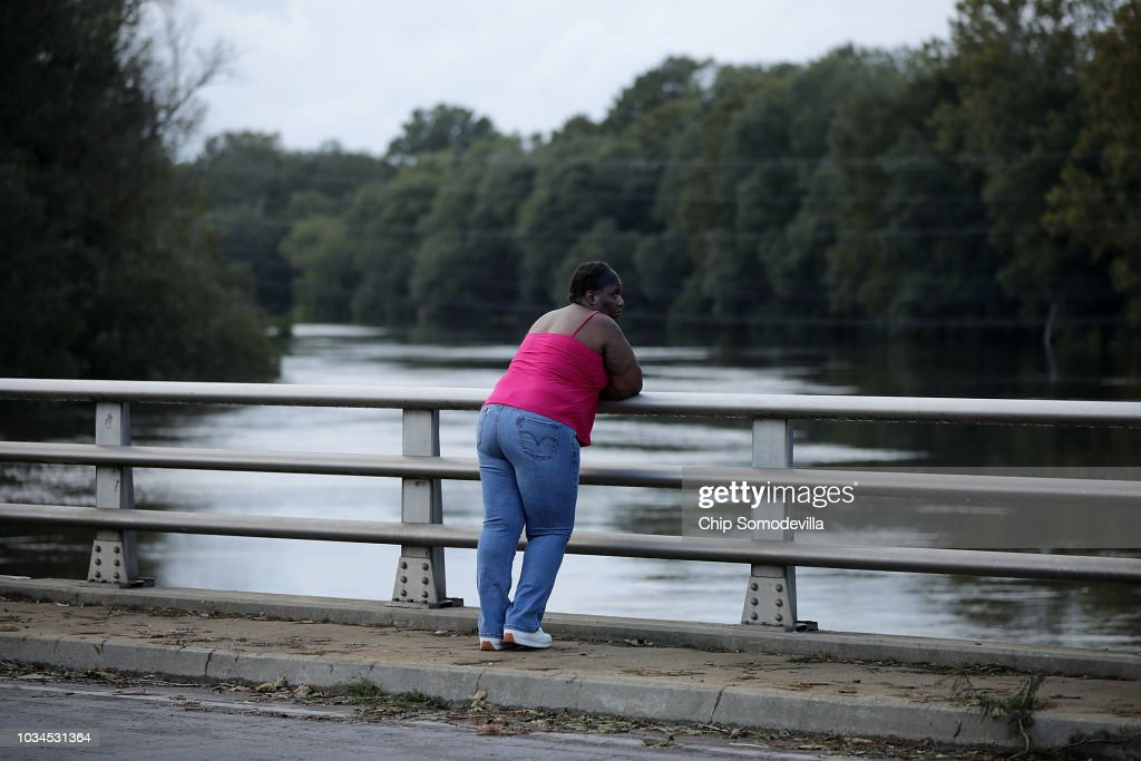 A woman pauses on the King Street bridge to watch the rising