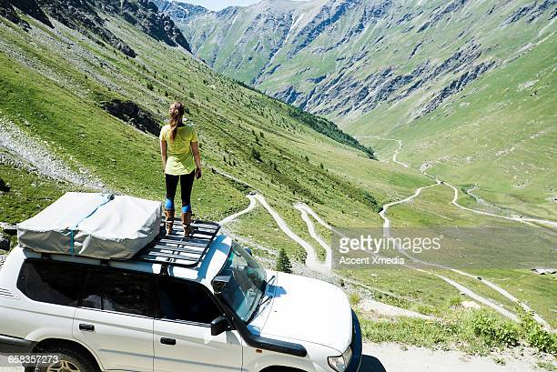 Woman pauses on top of 4x4,looks down road climbed