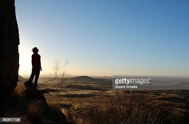 Woman pauses to look across desert landscape