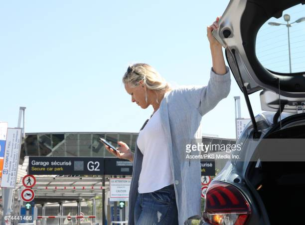 Woman pauses to text beside car tailgate, airport