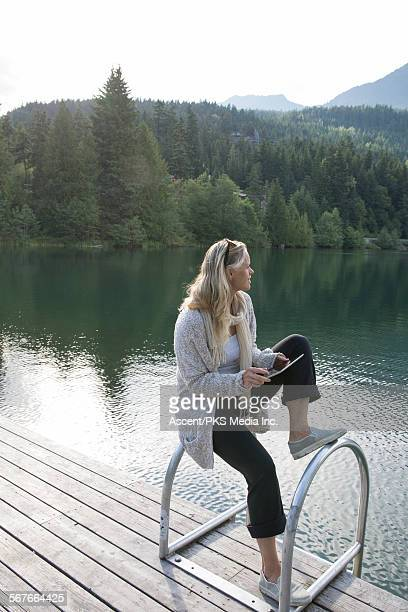 Woman pauses while using digital tablet, pier