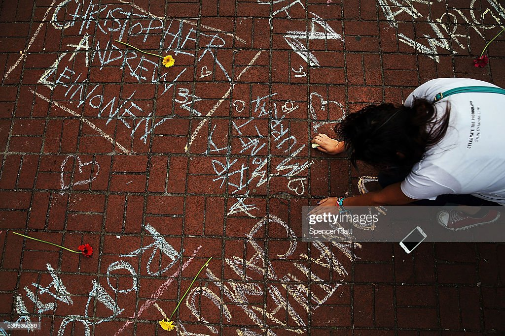 A woman pauses while writing the names of shooting victims in chalk in a park across from the iconic New York City gay and lesbian bar The Stonewall Inn on June 13, 2016 in New York City. An American-born man who had recently pledged allegiance to ISIS killed 50 people early Sunday at a gay nightclub in Orlando, Florida. The massacre is the deadliest mass shooting in United States history.