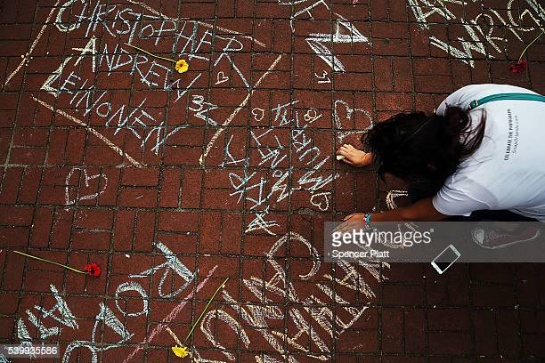 A woman pauses while writing the names of shooting victims in chalk in a park across from the iconic New York City gay and lesbian bar The Stonewall...