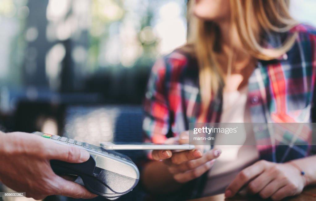 Frau mit Smartphone bezahlen : Stock-Foto