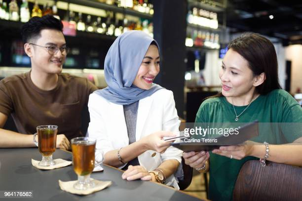 woman paying a restaurant bill - malaysian culture stock pictures, royalty-free photos & images