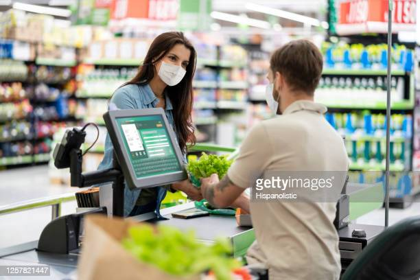 woman paying at the cashier in the supermarket while wearing a facemask - checkout stock pictures, royalty-free photos & images