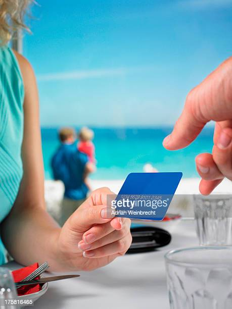 Woman paying beach restaurant with credit card