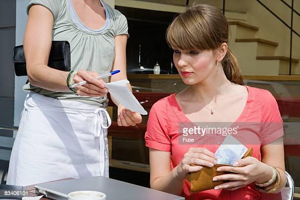 Woman Paying Bill at Cafe