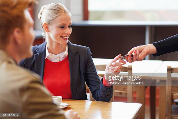 Woman paying bill by credit card in a restaurant