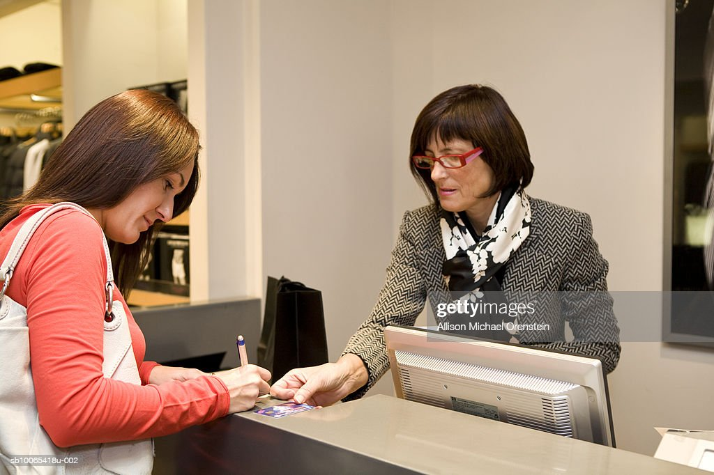 Woman paying bill with credit card at clothing store : Foto stock
