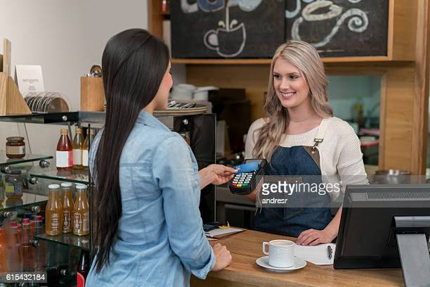 Woman paying by card at the cafe