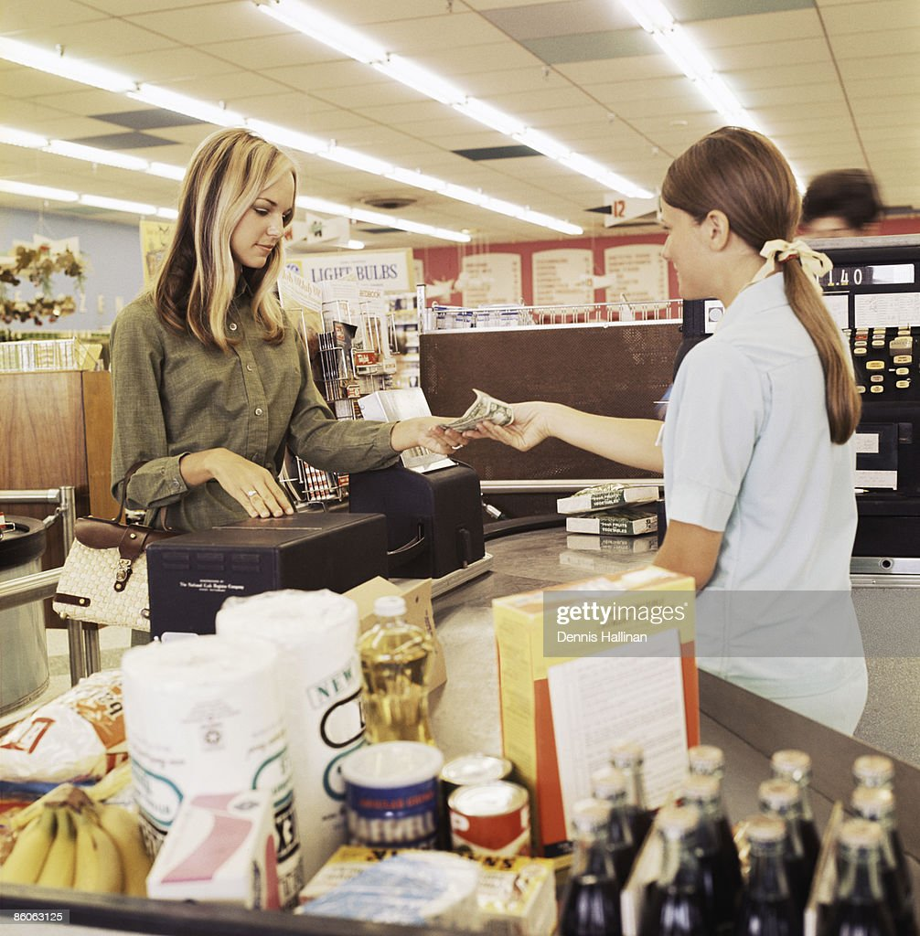 Woman paying cashier at grocery store : Bildbanksbilder