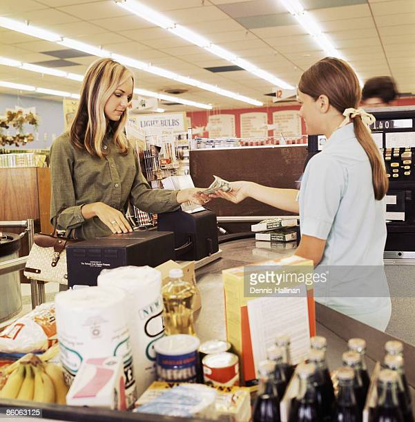 Woman paying cashier at grocery store