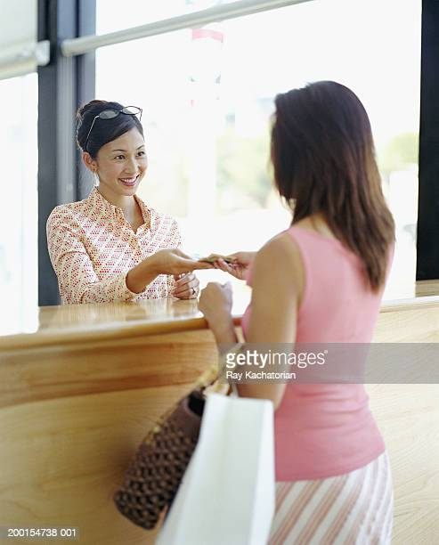 Woman paying cashier with Japanese Yen