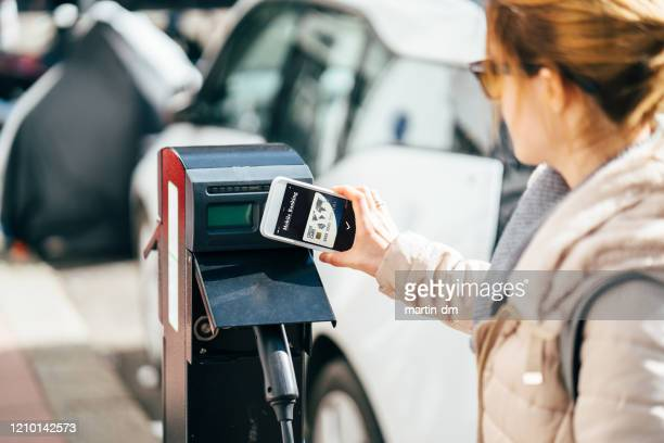 woman paying contactless for charging an electric car - electric vehicle charging station stock pictures, royalty-free photos & images