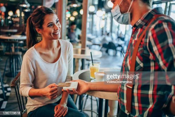 レストランでクレジットカードで非接触で支払う女性。 - 接近する 女性 ストックフォトと画像