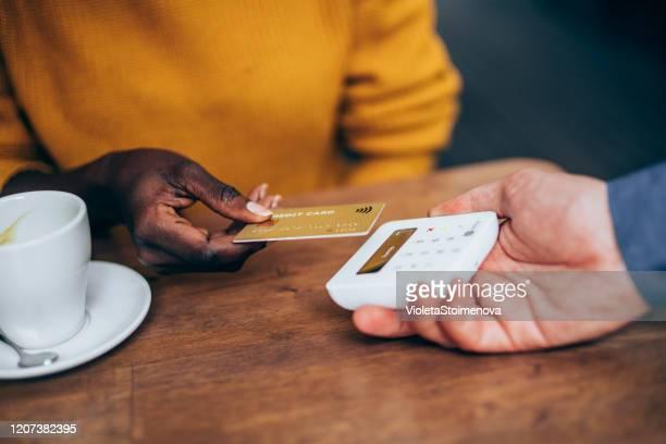 mulher pagando sem contato com cartão de crédito - passando - fotografias e filmes do acervo