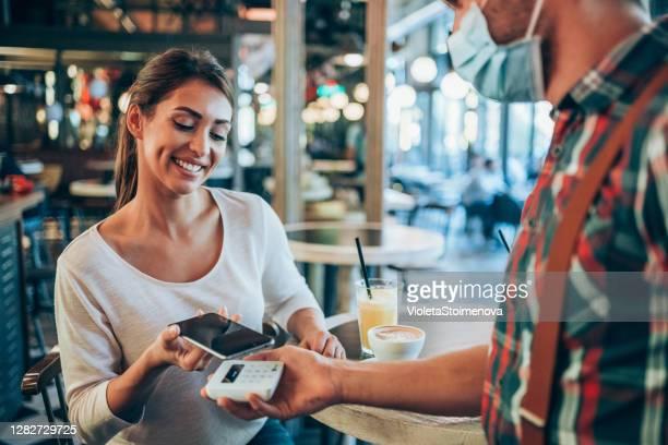 レストランでスマートフォンで非接触を支払う女性。 - 接近する 女性 ストックフォトと画像