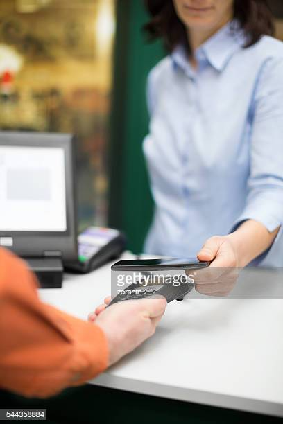 Woman paying contactless with smart phone